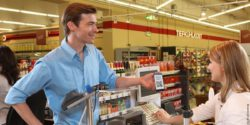 Image: man redeems coupon at check out zone ; copyright: acardo group AG