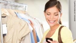 Photo: Woman shopping in a fashion store, looking at her smartphone; copyright: panthermedia.net / ariwasabi