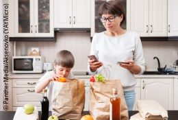 A woman is unpacking groceries in a kitchen with a little boy and holding a smartphone; copyright: PantherMedia/Aksenovko (YAYMicro)