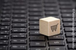 A little wooden block with a shopping cart symbol sitting on the keypad of a computer; copyright: PantherMedia / ra2studio