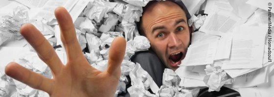 Businessman sinks into a pile of documents; copyright: PantherMedia / Nomadsoul1