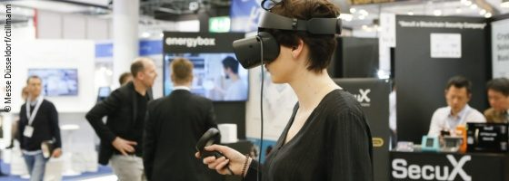 A young woman wearing VR glasses at a trade fair; copyright: Messe Düsseldorf/ctillmann