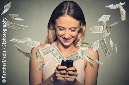 Woman on smartphone surrounded by banknotes; copyright: PantherMedia / SIphotography
