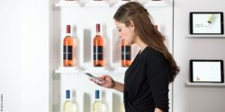 Picture: woman is checking her smartphone in front of a wine shelf; copyright: hybris software