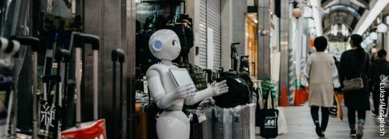 Robot Pepper stands in front of a shop on the street; copyright: Lukas/Unsplash