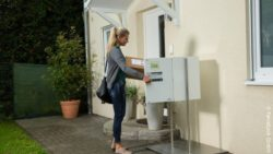 Photo: Woman with a picking up a parcel in front of her home out of a parcel locker; copyright: ParcelLock GmbH