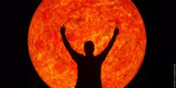 Picture: man with arms to the sky in front of red sun; copyright: Jens Bredehorn/pixelio.de