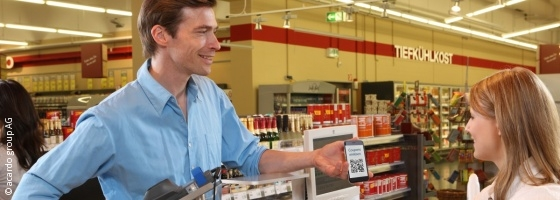 Photo: Young man redeems coupon at checkout zone