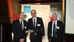 Picture: Christian Schallenberg (l.) and Thomas Friedl, CEO of REWE Systems (mi.) receive the award; copyright: EHI Retail Institute