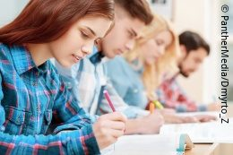 Several young people sit next to each other at a desk and write; copyright: PantherMedia/Dmyrto_Z