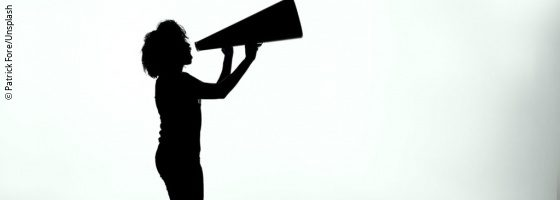 A silhouette of a woman calling into a megaphone; copyright: Patrick Fore/Unsplash