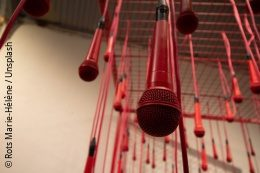 Several red microphones hanging from a ceiling in an installation copyright: Rots Marie-Hélène / Unsplash