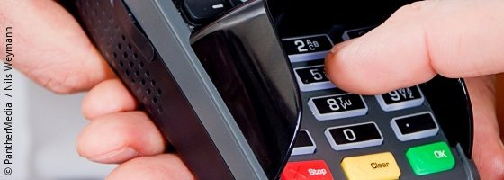 Person typing in pin number on payment device; copyright: PantherMedia  / Nils Weymann