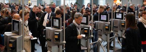 A large mass of people are going through turnstiles at a trade fair; copyright: ctillmann/Messe Düsseldorf