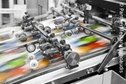 Big printing machine with colored prints coming out; copyright: Bildagentur PantherMedia/silvanoaudis