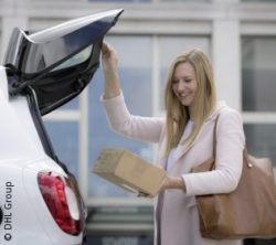 Image: woman takes out a package from her car trunk; copyright: DHL Group