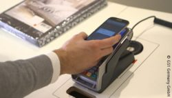 Picture: Smartphone is held over a payment terminal; copyright: GS1 Germany GmbH