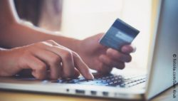 Photo: Man using his credit card while shopping online; copyright: fotolia.com/Ivan Kruk